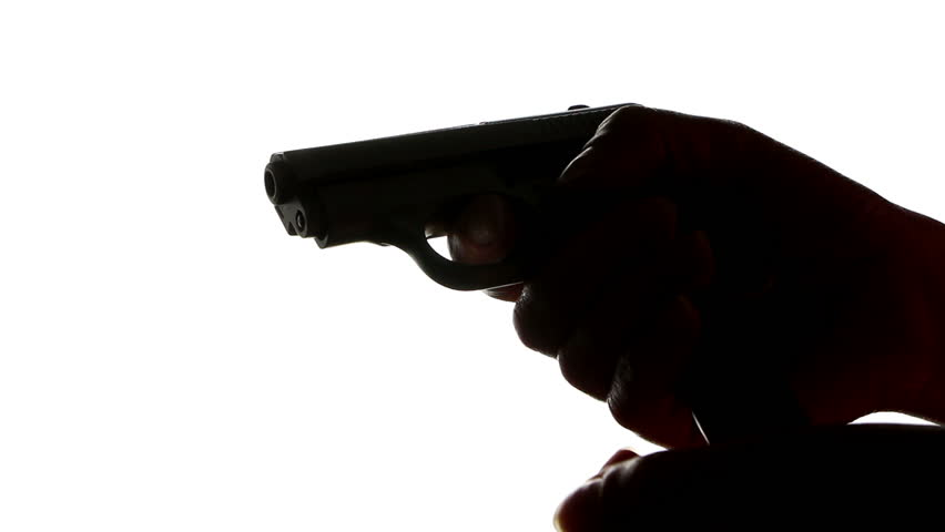 Silhouette of hands loading a gun and shooting