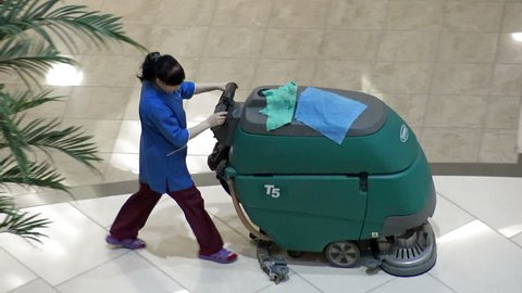 "St. Petersburg, Russia, 13 november, 2015: shopping center ""Atlantic city"", cleaning of the floors in the common area. Work cleaners. Woman worker maid. Apparatus for cleaning. The service of hotel."