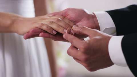 gold wedding rings and hands of just married couple  Close up on hand of a man put on an engagement ring on the finger of the bride ,Shot on RED Digital Cinema Camera in 4K