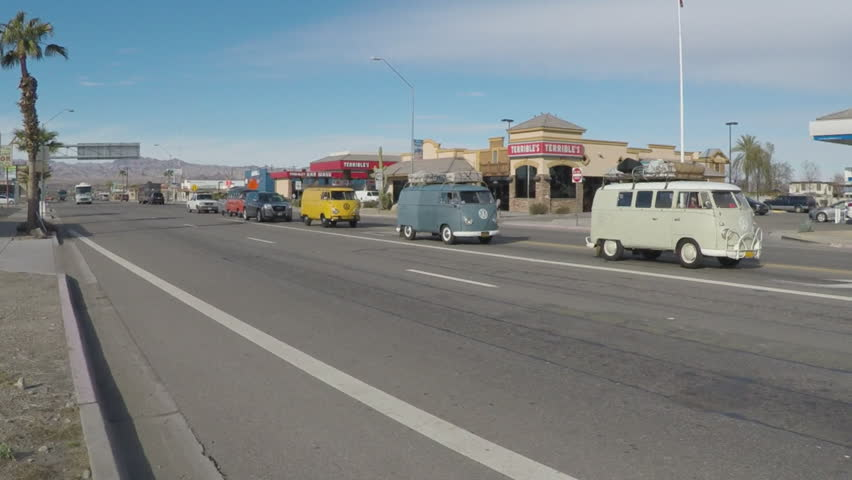 """PARKER, AZ/USA - January 22, 2016: Old time camper buses eclipsed by a huge modern recreational vehicle. A giant RV passes by as a line of 1960""""s Volkswagen vans roll down the street."""