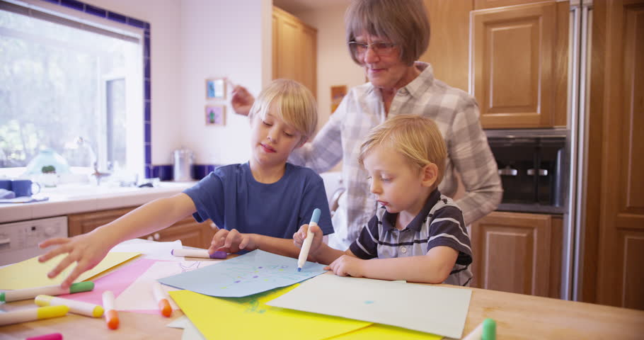 Elderly Babysitter Drawing With Two Cute White Children Stock ...