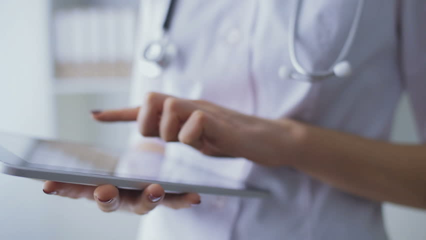 Close-up of hands of the young nurse working with the tablet. In slow motion