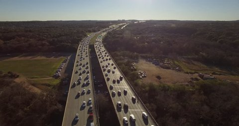 The camera hovers high above  the north and south sides of Austin, Texas' Mopac highway during rush hour traffic.  The traffic moves slowly as cars are heading home from a long day at work.