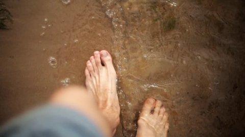 Man walk on sand beach, waves gentle wash his feet. Summer. First person view