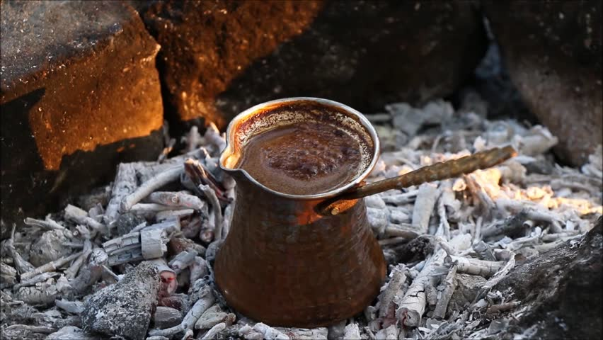 Turkish coffee cooking on embers. Turkish coffee cooked on embers.  Ember Turkish coffee. Roasted Turkish coffee. Traditional nubian coffee making. Coffee turk on the coal. Making coffee on embers.