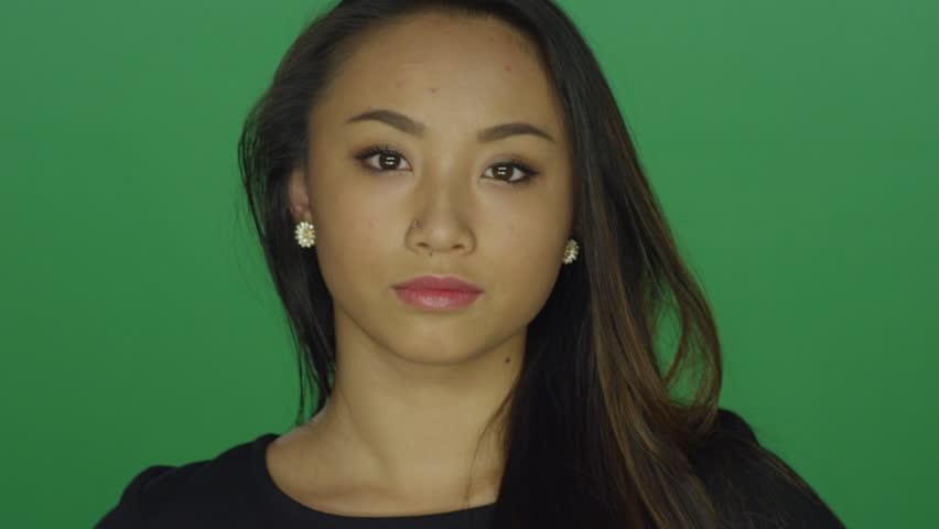 Beautiful young woman looking sad, on a green screen studio background | Shutterstock HD Video #14361445