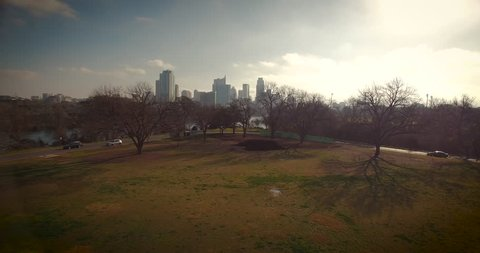 The camera flies over Zilker Park at a low altitude, just barely clears some trees then gains altitude to reveal Lady Bird Lake in Austin, Texas.  Paddle boarders are seen on the water.
