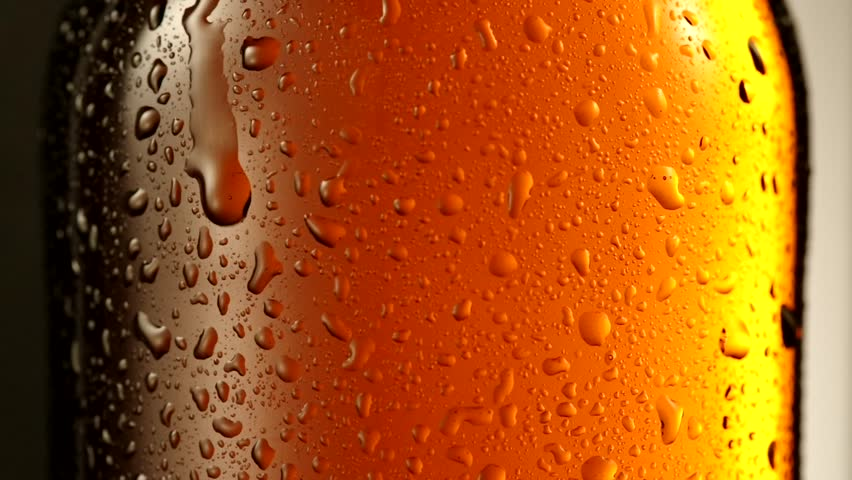 Drop of condensate drains on a bottle of beer.