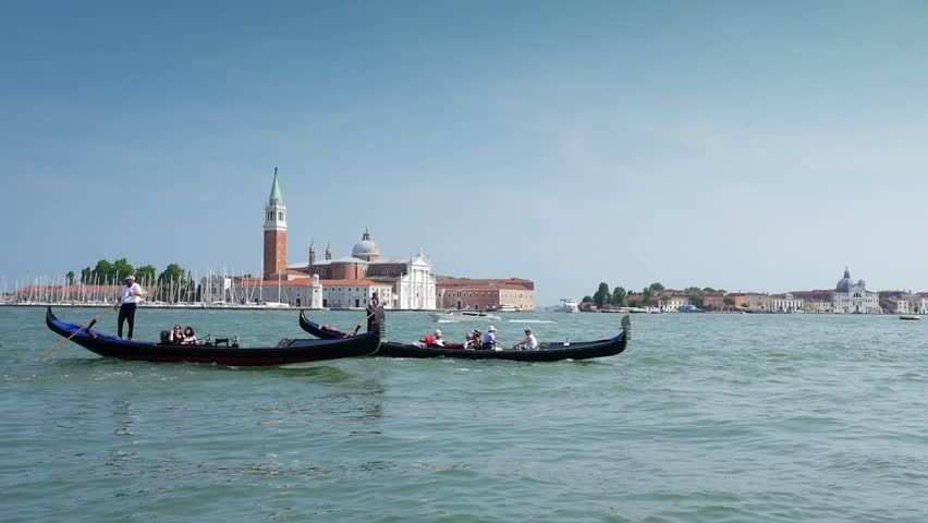 VENICE, ITALY - CIRCA JULY 2015: Pair gondolas rowed by a gondoliers through the San Marco Canal in Venice, Italy. San Giorgio Maggiore on the background.