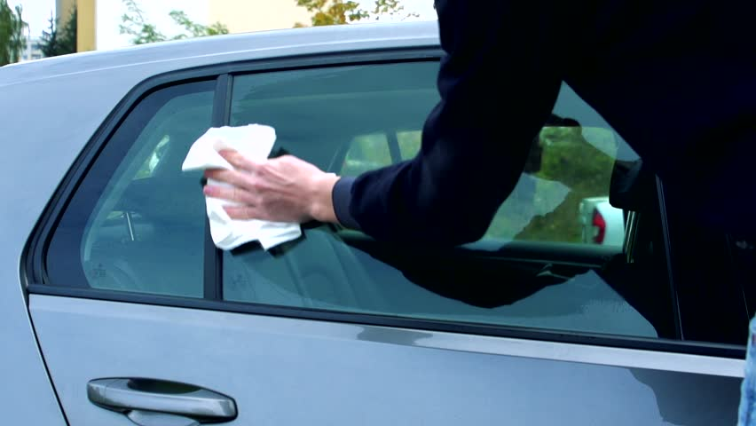 Slowmotion man dusts and polishes a window of car