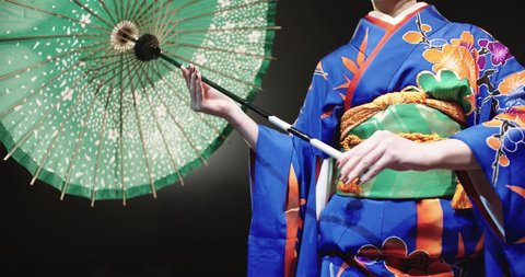 4K beautiful Japanese geisha dancing on stage and posing for the camera with an umbrella, in slow motion