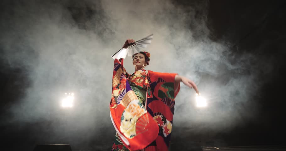 4K beautiful Japanese geisha dancing on stage and posing for the camera,the smoke in the background, slow motion | Shutterstock Video #14442808