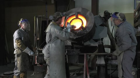 Lost wax bronze casting in a foundry/pouring the molten metal in the casting crucible