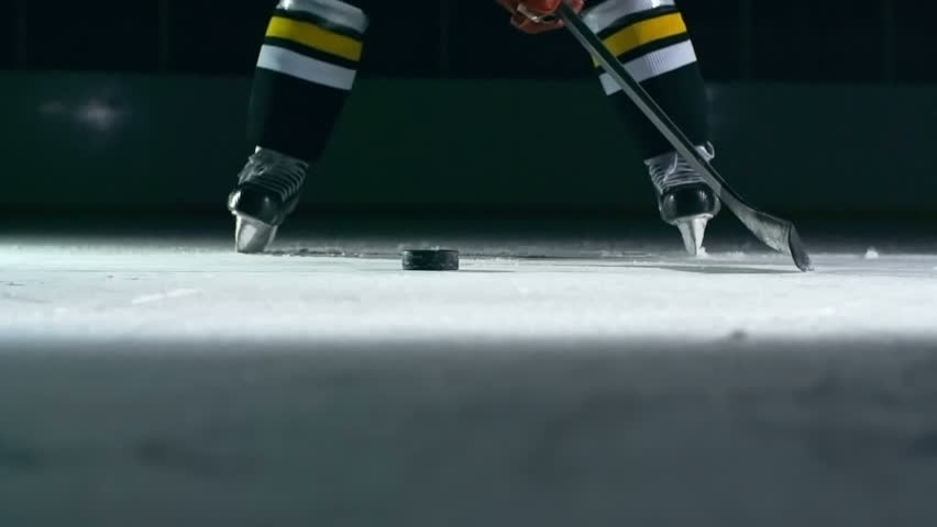 Closeup of hockey player slapping a puck with his stick in slow motion  | Shutterstock Video #14497159