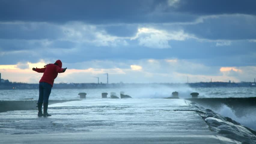 Woman standing near storm waves hitting the pier | Shutterstock HD Video #14500492
