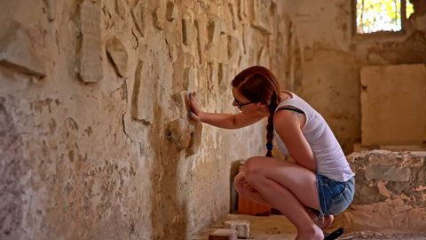 Person cleaning dust from old writings on wall. Young woman interested in ancient history of Carthage civilization, looking at writings on wall of small tomb.