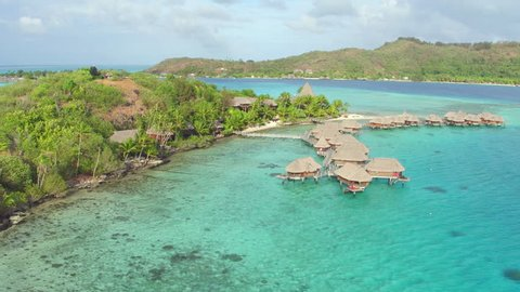 AERIAL: Flying around fantastic resort hotel with luxury overwater villas on a small private island with secluded white sand beaches in front of exotic Bora Bora island