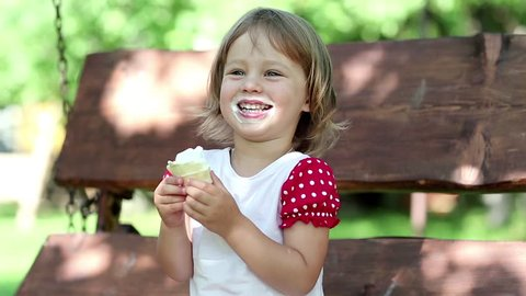 Cute little girl sits on the bench eats ice cream and laughs. Girl with ice cream. Funny little girl with ice cream. Child eats ice cream