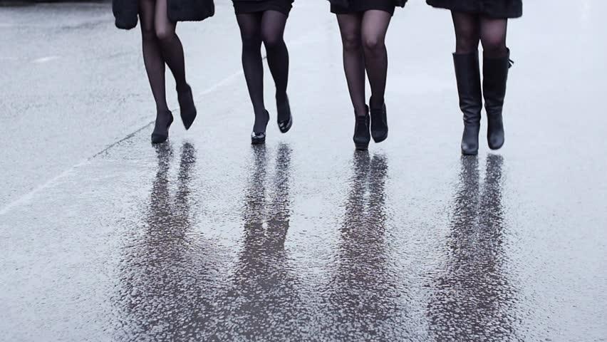 Legs of four woman in shoe on heels walk in lockstep on wet asphalt. Slow motion