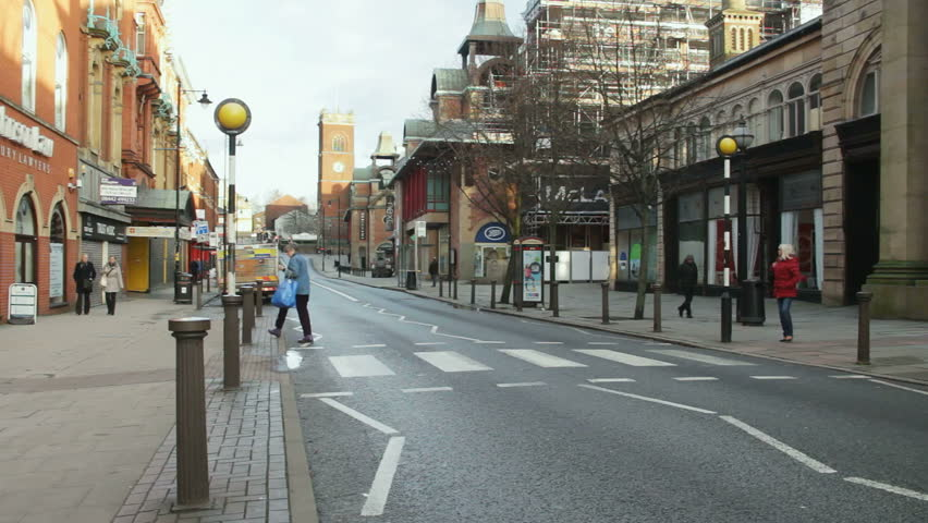 Bolton, Lancashire, UK. February 2016. Mid-adult woman using the zebra crossing on Knowsley Street in Bolton town centre, Lancashire on a weekday morning in 2016.