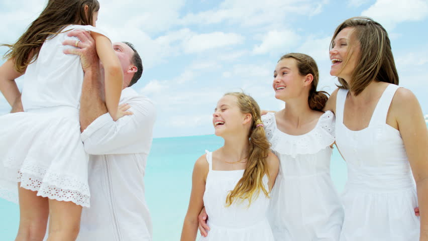 Loving young Caucasian parents female children healthy outdoor freedom carefree luxury beach ocean shallows happy advertisement RED DRAGON   Shutterstock HD Video #14556535