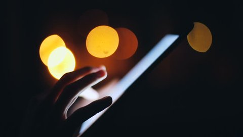 Woman finger touching tablet touchscreen at night time. Close up