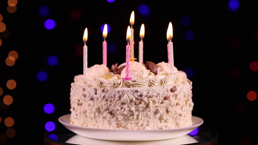 Happy Birthday Cake With Burning Candles In Front Of Black Background Flashing Lights