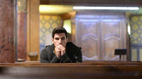 Young man praying in church