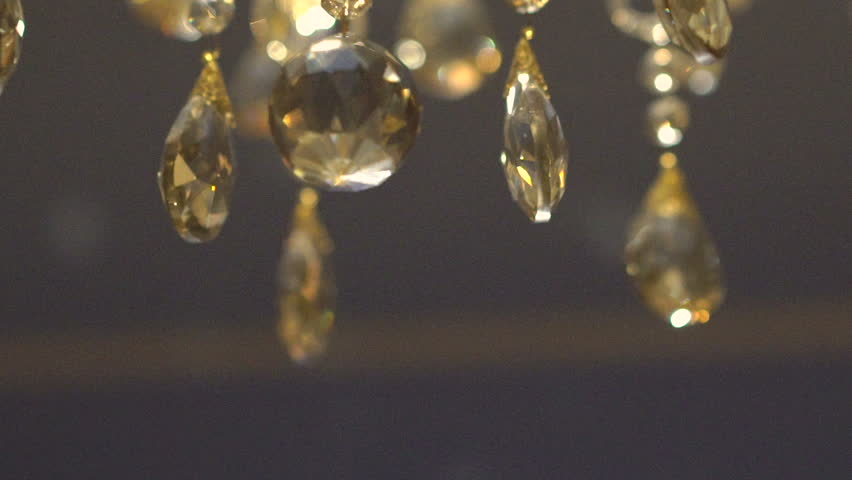 Close up on a crystal chandelier swaying back and forth in a moving of a luxury crystal gold chandelier beautyful background slowly hd stock footage mozeypictures Gallery