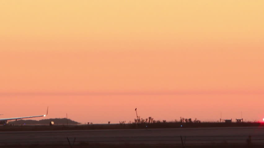 HD footage of a twin engine plane taking off in silhouette against an orange sky.