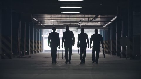 Black silhouettes of four men walking towards the camera in the car parking
