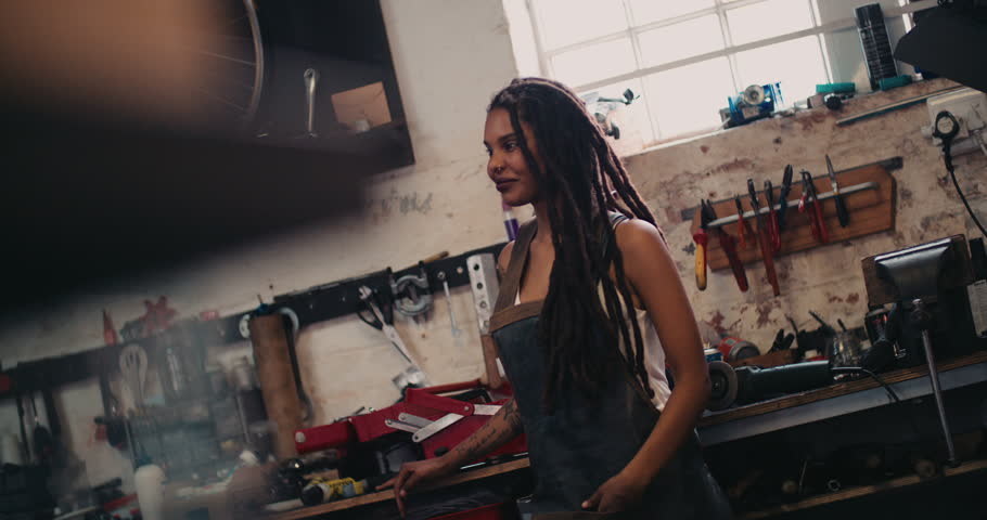 Smiling afro-american craftswoman with dreadlocks standing against her work bench in a leather apron with her tools around her in her workshop