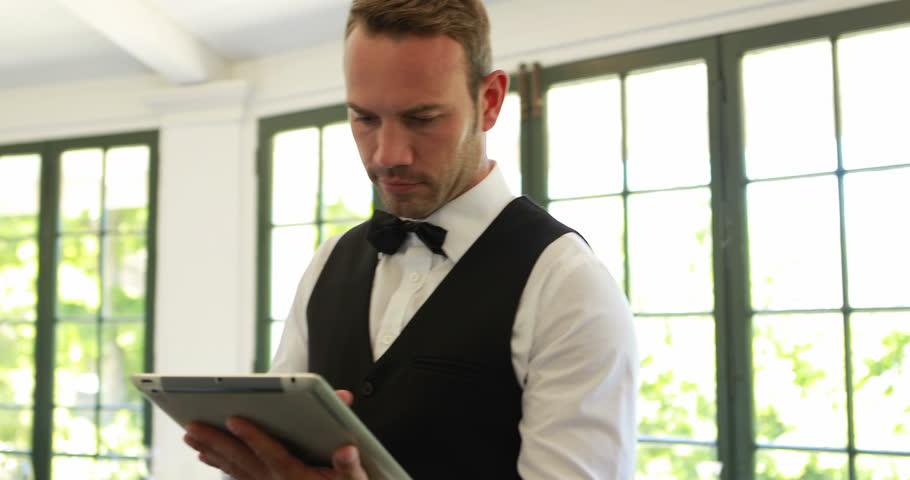 Handsome waiter using tablet in the restaurant