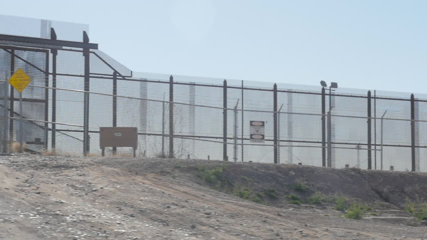Panning shot of the fence along the border of the US and Mexico. Mid shot there is a border patrol SUV sitting and guarding the border.