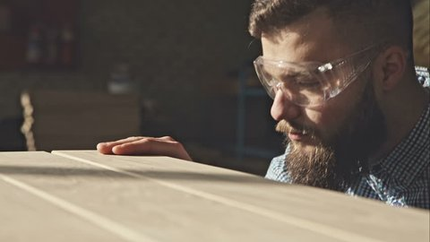 A young bearded carpenter checks the quality of the boards in the sun. RAW video record.