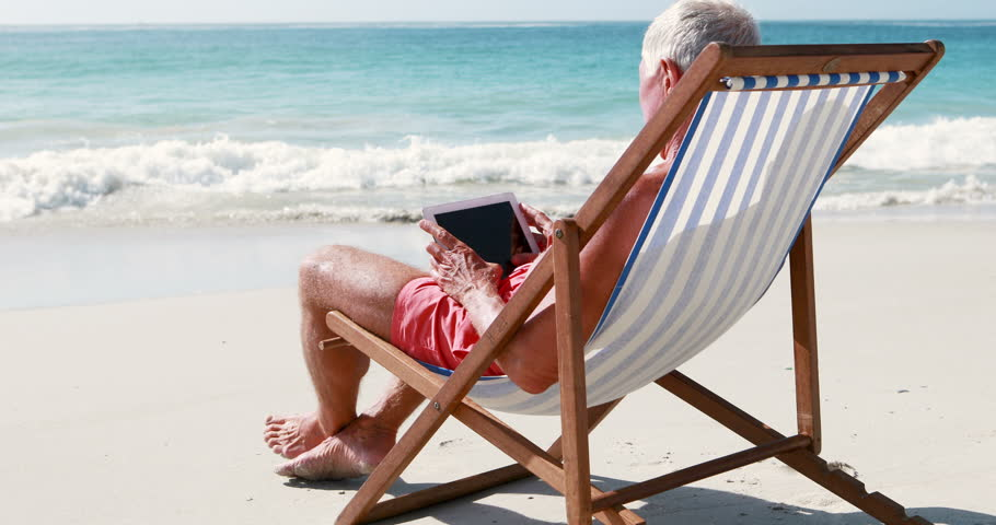 Retired Old Man Using Tablet While Lying On Deckchair The Beach
