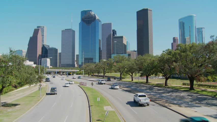 Cars drive along a highway leading into downtown Houston.