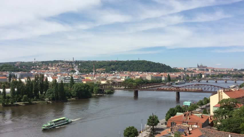 A boat is moving on the river and the tram is moving toward on the street. A river cruise is a way to see different sights of Prague. This is a view from the hill at Vysehrad fortress in Prague.   Shutterstock HD Video #14791975