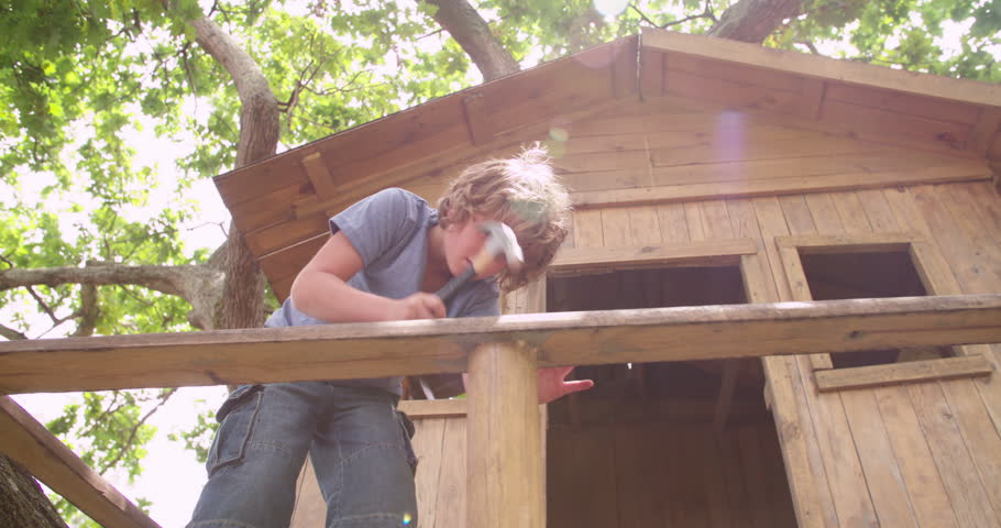 Young boy using a hammer and nail to do some repairs to his rustic wooden treehouse on a summer day