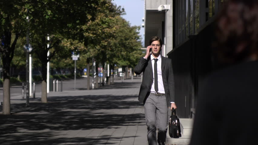 Young businessman talking on mobile phone and walking in the street. Slow motion