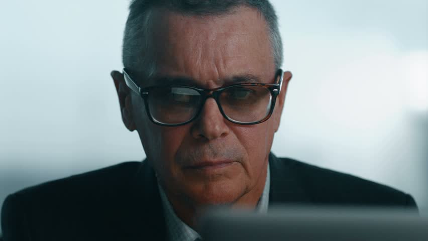 elderly businessman working with computer in modern office.  he takes off his glasses and peers at the screen