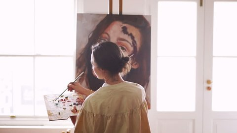 Vintage style rearview shot of a young woman artist mixing paint on a wooden palette while working on a canvas that is resting on an easel placed between the windows of her studio