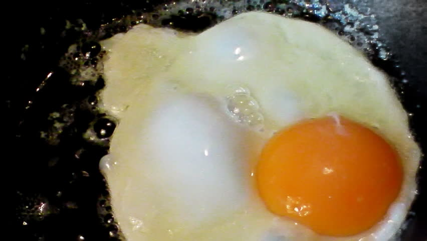Fried eggs preparation on a frying pan