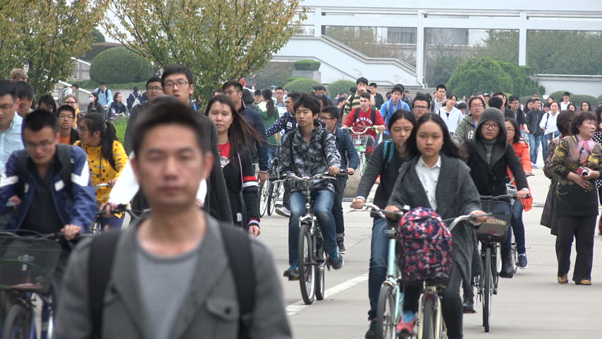 SHANGHAI, CHINA - 4 NOVEMBER 2015: Students walk and cycle across the campus of the Shanghai University campus during lunch break, college education in China