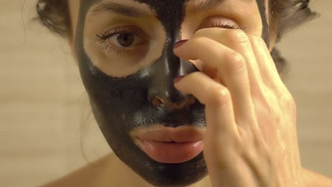 Beautiful woman removing black face pack from her face