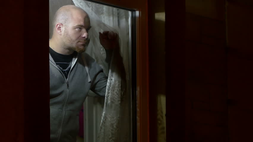 stock video of a bald man in his forties looking in the mirror