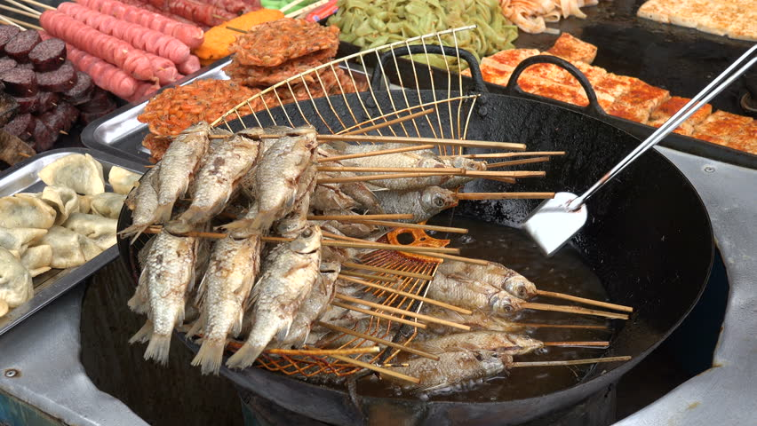 Fenghuang china september 2015 frying fish skewers for Cheap koi food
