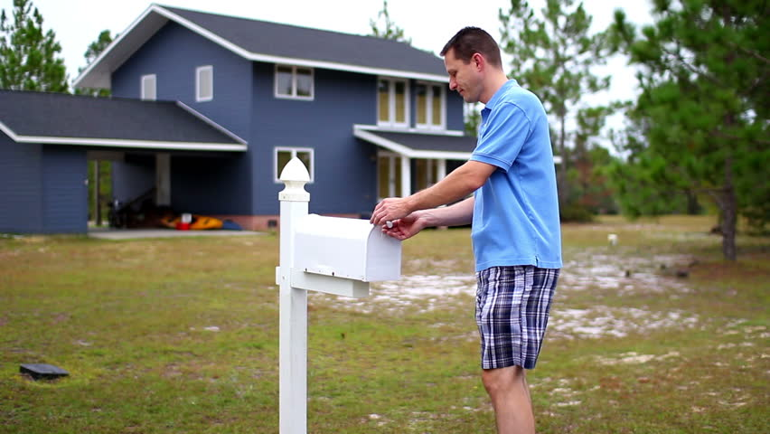 A man checks his mail outside of his house.