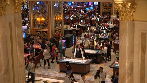 MACAU - 24 OCTOBER 2015: Mainland Chinese visitors gamble inside the Venetian Macao, one of the largest and most popular casino and hotel resorts in the world