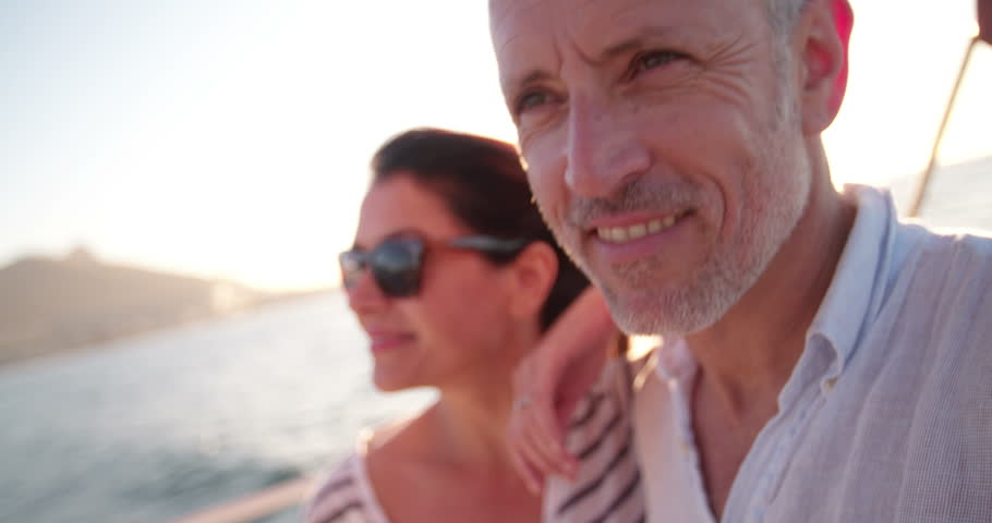 Close up shot of a retired couple looking lovingly at the ocean while enjoying a cruise on a yacht with clear blue sky and bright afternoon sunflare | Shutterstock HD Video #14888995
